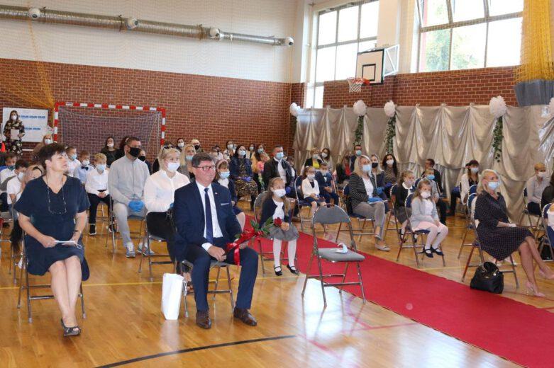 Zdjęcie wykonane na inauguracji roku szkolnego 2021/2022. Na sali gimnastycznej siedzą rodzice pierwszoklasistów, uczniowie klas pierwszych oraz wójt gminy Jerzmanowa.